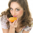 fille heureuse, manger une orange sur fond blanc — Photo