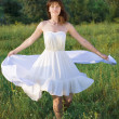 Stock Photo: Girl in white dress twirling round