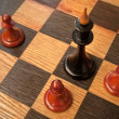Black king and red pawns — Stock Photo #4091287