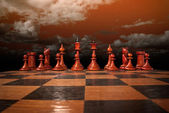 Chess figures under a red sk — Stock Photo