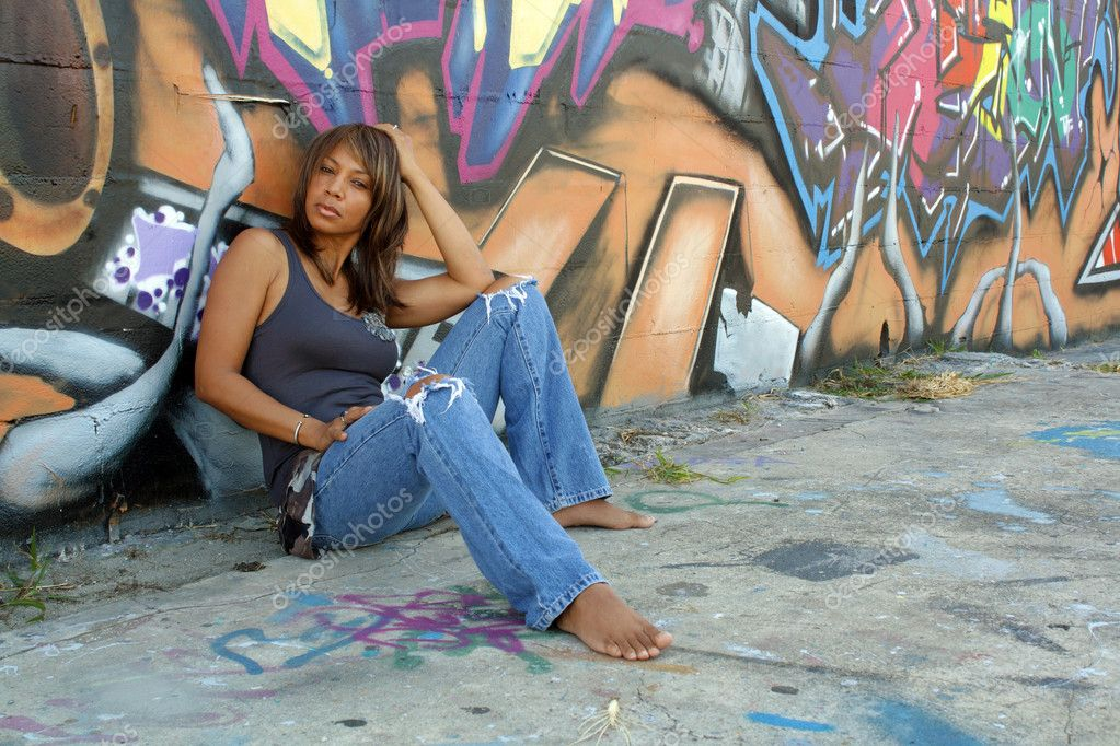 A lovely mature black woman, wearing tattered jeans, sits in front of a wall of graffiti art. — Stock Photo #4087258