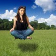 Teen Girl Sits Suspended Above a Grassy Field — Stock Photo