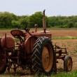 Old farm tractor in the field - Stock Photo