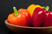 Three Bell Peppers in a wood bowl — Stock Photo
