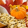 Stock Photo: Toasted pumpkin seeds spilling from a yellow bowl