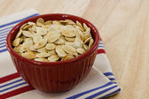 Red bowl brimming with toasted pumpkin seeds — Stock Photo