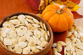 Close up of healthy pumpkin seeds and pumpkin against colorful autumn accen — Stock Photo