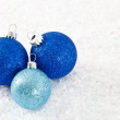 Three Blue Glittery Ornaments on Snowy Background — Stock Photo