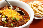 Hearty chili with cheese and scallions — Stock Photo