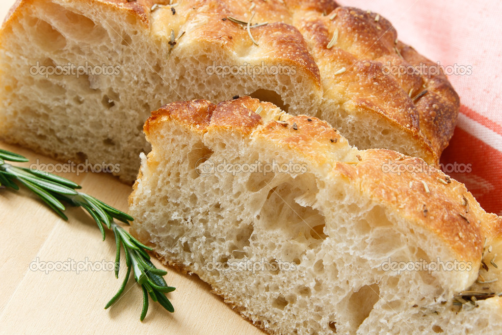 Close up of sliced artisan focaccia bread with a sprig of rosemary  Stock Photo #5375506