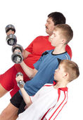 Father and two sons holding dumbbells — Stock Photo