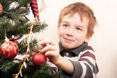 Boy decorates Christmas tree — Foto de Stock