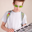 Stock Photo: Teen plays on synthesizer