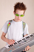 Teen plays on synthesizer — Stock Photo