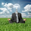 Businessman in lotus pose and lamp-head in grass — Stock Photo #4054374