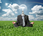 Businessman in lotus pose and lamp-head in grass — Stock Photo