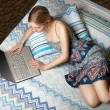Girl with laptop on the bed — Stockfoto