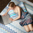 Girl with laptop on the bed — Stock Photo