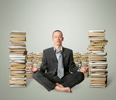 Businessman in lotus pose with many books near — Stock Photo