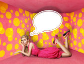 Překvapený blondýnka v růžových šatech s myšlenkou bublina — Stock fotografie