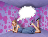 Surprised blonde in blue dress with thought bubble — Stock Photo