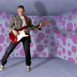 Punk man in cardboard room with the guitar — Stockfoto