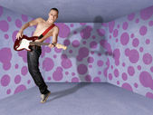 Punk man in cardboard room with the guitar — Stock Photo