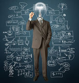 Businessman with lamp-head and marker — Stockfoto