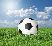 Soccer ball in green grass and blue cloudly sky — Stock Photo