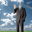 Businessman with lamp-head holding blank card outdoors — Stock Photo