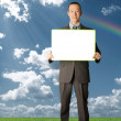 Happy businessman holding blank white card outdoors — Stock fotografie