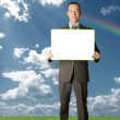Happy businessman holding blank white card outdoors — Stock Photo #5116387