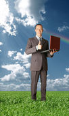 Full length portrait of businessman with laptop outdoor — Stock Photo