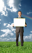 Happy businessman holding blank white card outdoors — Stock Photo