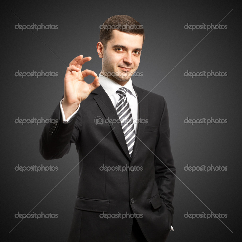 Happy businessman in suit shows OK, looking on camera  Stock Photo #5221931