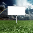Billboard and green grass and blue cloudly sky — Stockfoto