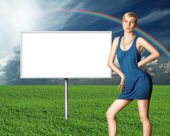 Billboard and sexy blonde on green grass and blue cloudly sky — Stock Photo
