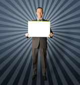 Happy businessman holding blank white card — Stock Photo