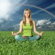 Blonde in lotus pose in green grass — Stock Photo #5370564