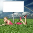 Blonde in pink dress in green grass — Stock Photo