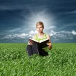 Stock Photo: College girl reading big book in green grass