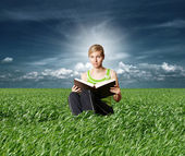 College girl reading big book in green grass — Stock Photo