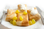 Pancakes with filling on plate with sour cream and grapes — Stock fotografie