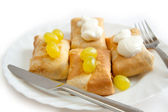 Pancakes with filling on plate with sour cream and grapes — 图库照片