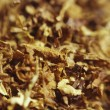 Loose cuts of dried tobacco form golden background texture .Shallow DOF. — Stock Photo