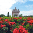 Patuxay, the victory gate of Vientianered with red flower on Lao - Stock Photo