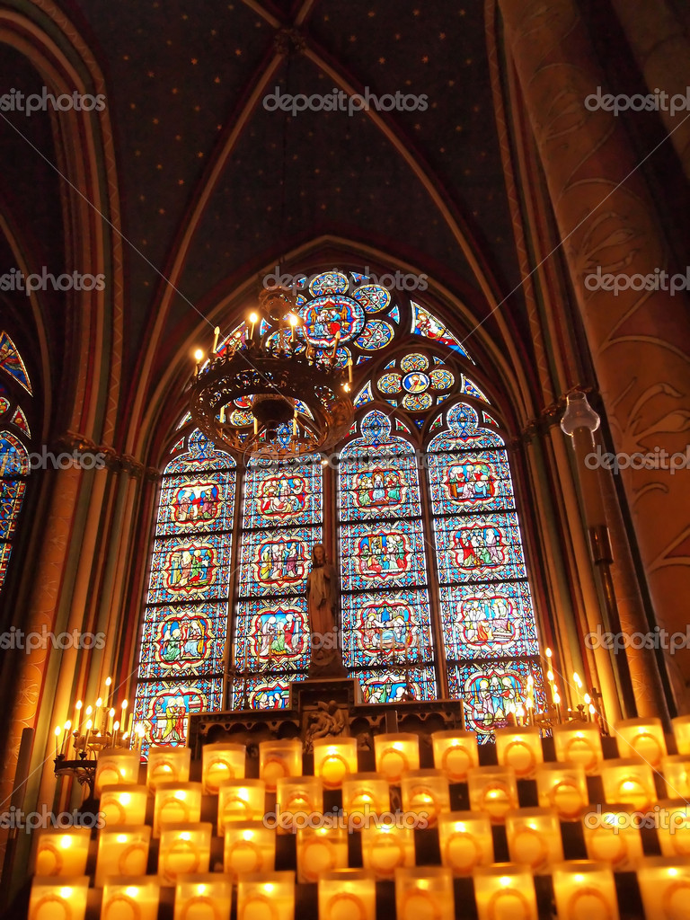 Candles in front of a stained window at Notre Dame Cathedral in Paris, France.   Stock Photo #4328314
