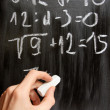 Hand writes mathematical equations on black blackboard — Stock Photo