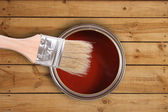 Red paint can with brush on wooden floor — Stok fotoğraf