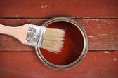 Red paint can with brush on wooden plank background — Stock Photo